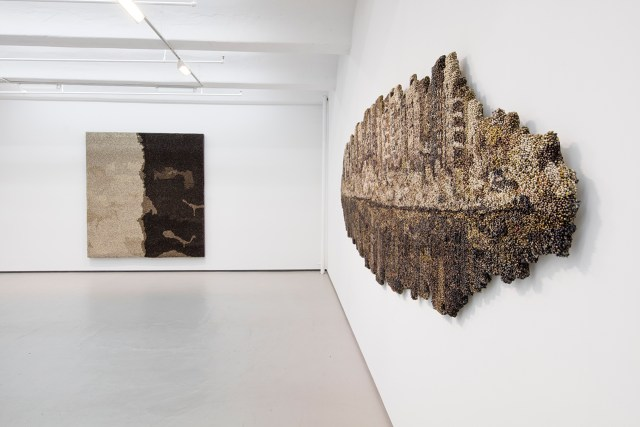 """Installation view, 'Vibha Galhotra: ABSUR –CITY –PITY -DITY' at Jack Shainman Gallery, with (left to right): """"Untitled"""" (from the 'Flow' series, 2013), metal ghungroos on fabric stretched over wood panel, 95 x 87 x 3 inch; and """"Majnu Ka Tila"""" (2015), nickel coated ghungroos, fabric, wood, polyurethane coat, 52 x 178 x 2 in (click to enlarge)"""