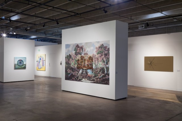 """Installation view of 'Monumental' at RedLine with, at center, Suchitra Mattai, """"Her earthly gains,"""" embroidered needlepoint, 42 x 26 in mounted on a 10 x 6.2 ft pixelized print"""