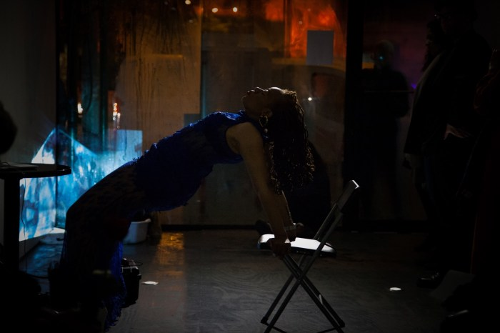 Ayana Evans doing chair dips in the gallery. Photo by Ventiko