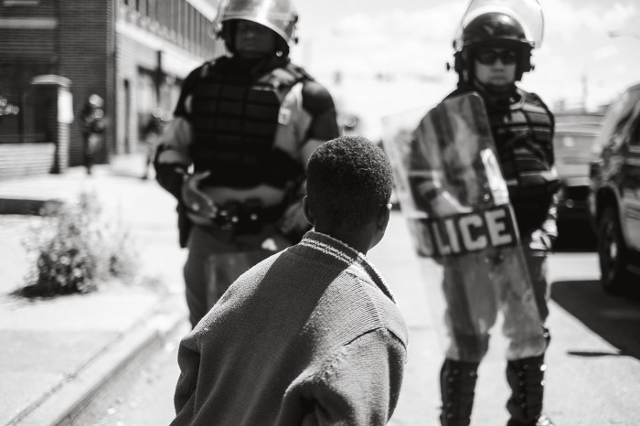 """Devin Allen, """"Young boy standing in front of police officers at a blockade, North Avenue, West Baltimore"""" (2015). (All photos courtesy of the artist and Aperture Magazine)"""