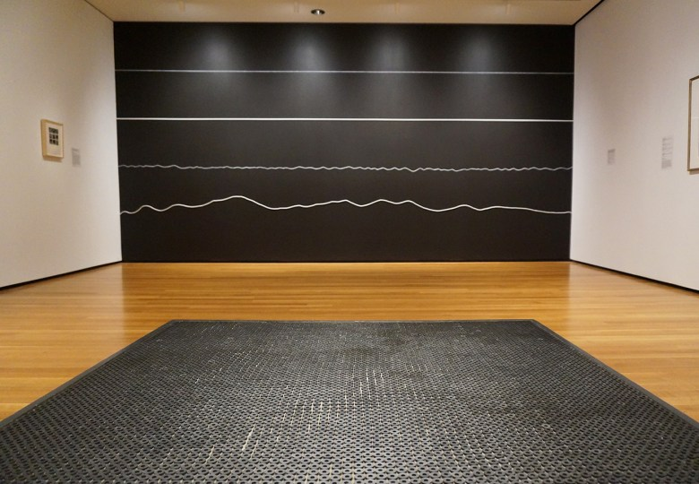 """Foreground: Eva Hesse, """"Washer Table"""" (1967), rubber washers, painted wood, and metal; background: Sol LeWitt, """"Wall Drawing #325: On a black wall, white horizontal lines: two straight—one crayon, one wood; two not-straight—one crayon, one rope. The lines are equally spaced"""" (1980), white crayon, white wood, white rope on black wall"""