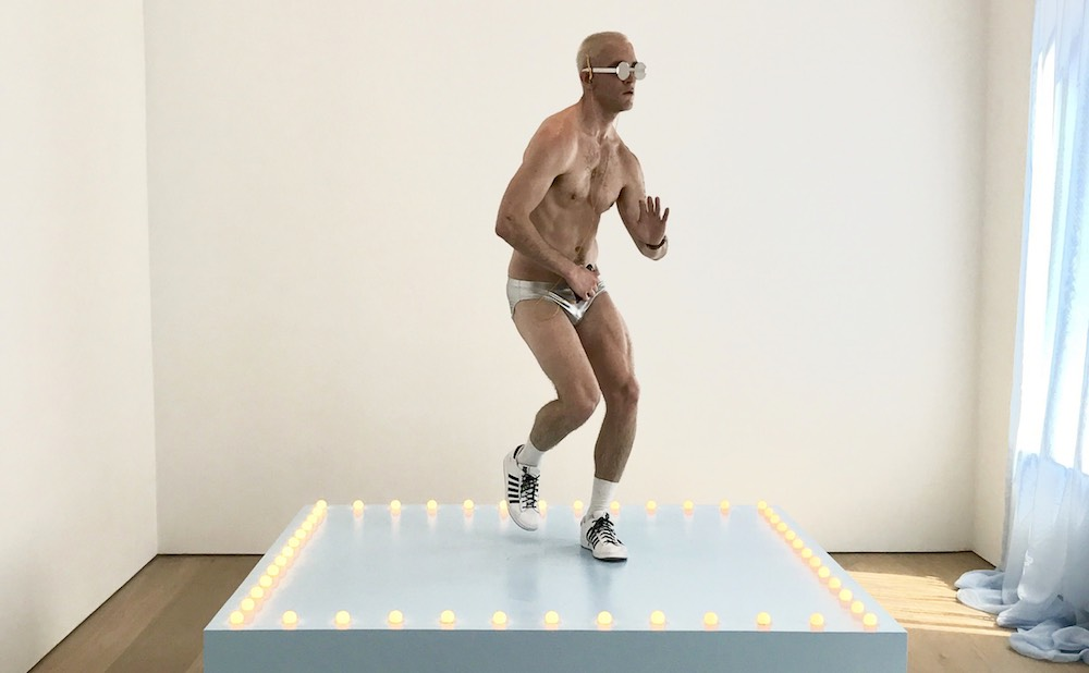 """Felix Gonzalez-Torres, """"Untitled"""" (Go-Go Dancing Platform) (1991), wood, light bulbs, acrylic paint, and Go-Go dancer in silver lamé bikini, sneakers, and personal listening device; overall dimensions vary with installation; platform: 21 1/2 x 72 x 72 in (photo by the author for Hyperallergic)"""