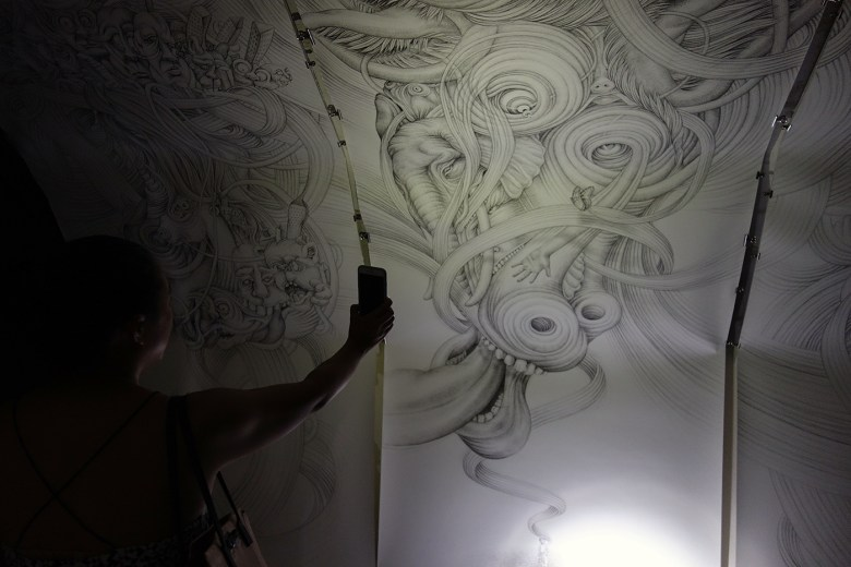 Installation view of ink drawings by Eeva Honkanen, illuminated by iPhone flashlight