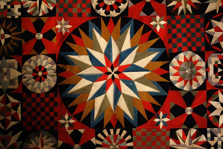 Detail of Soldier's Quilt by an unidentified artist (Crimea, India, or United Kingdom, 1850–75), wool, probably from military uniforms; inlaid; hand-appliquéd with buttonhole fabric discs (photo by the author for Hyperallergic)