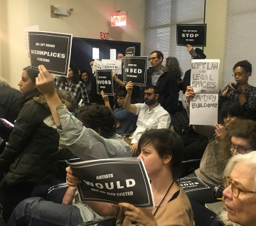 A public meeting of New York City's Loft Board on January 18, 2018 proceeds while protesters in the audience brandish signs.