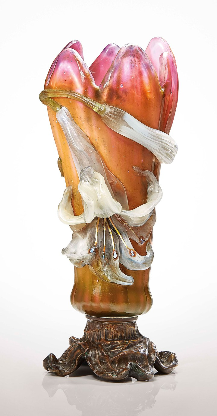 "Émile Gallé, a ""Lys"" vase, the vessel in the form of a lily, overlaid, fire-polished, polished to reveal a graduation in color, applied flower and bud with wheel-carved detail, marquetry stamens, patinated bronze base with snail detail, 12 3/4 inches high (image courtesy Christie's)"