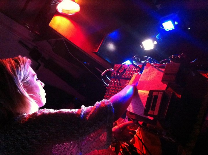 A blonde woman, lit by orange and blue light in a darkened club, turns knob on an analog synthesizer mid-performance.