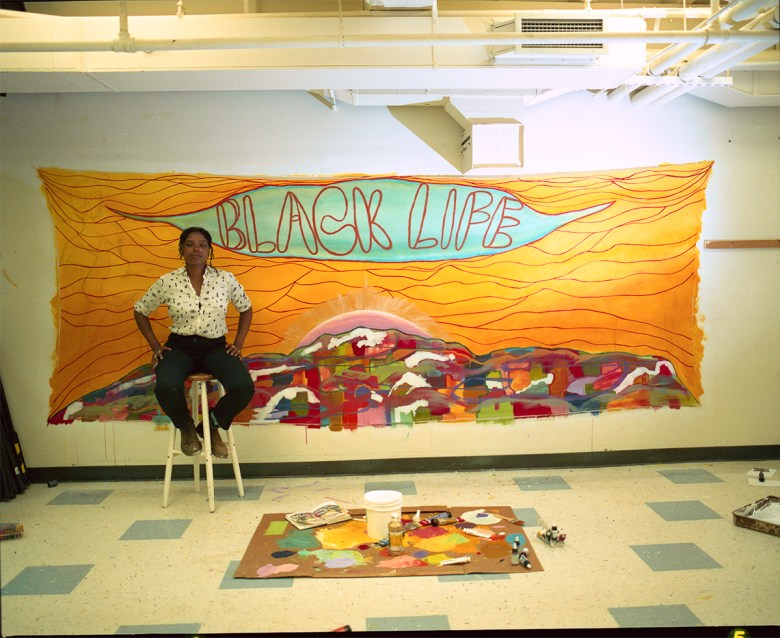 "View onto a classroom-like space. At the foreground, on the floor, rests paint materials. Behind, sitting on a stool, is the artist, a femme-presenting Black person. Behind this person hangs a large, colourful artwork. There is an orange sky with red lines, above an abstract, multi-coloured city skyline with the sun peaking above. At the top, In red outlined text behind a blue background reads ""BLACK LIFE."""