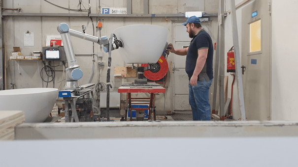 Worker using the robotiq sanding kit with Universal robots to sand a bath