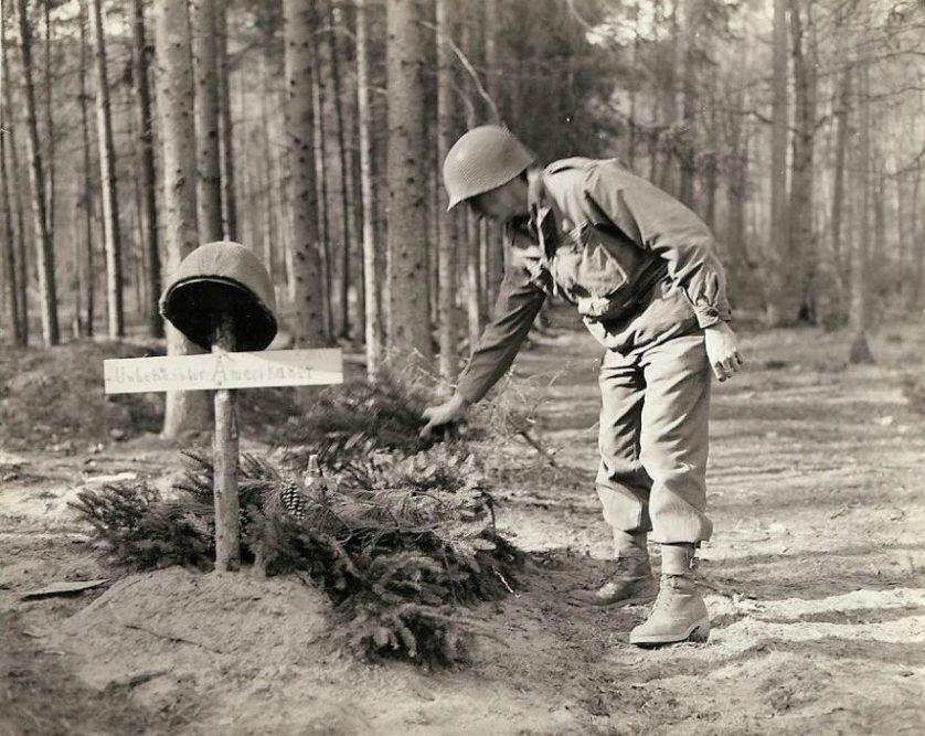 Um soldado americano examina o túmulo de outro soldado americano desconhecido, que foi enterrado pelo inimigo. O primeiro que notou o túmulo o decorou com morteiros e samambaias.
