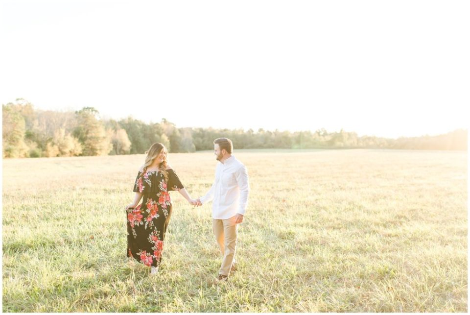 engagement session in a field at sunset golden hour walking towards the camera