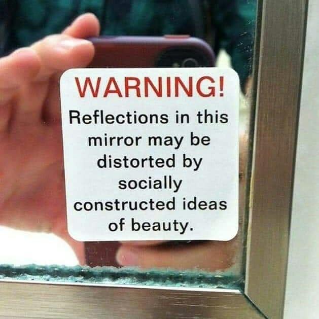 une étiquette sur un miroir qui prévient que ce miroir peut déformer l'image construite sur une idée de ce que la société a de la beauté.