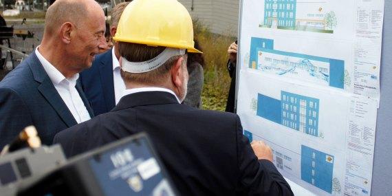 Bild Wolfgang Tiefensee (li.) und Dr. Ulrich Palzer (Mitte) vor dem Bauplan des HySON-Institutsgebäudes