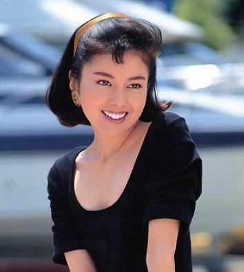 黒いトップスを着て金色のカチューシャをつける若い頃の沢口靖子