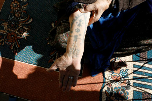 Hulu Aydogdu, 87, poses as she speaks about her tattoos at her home in Kisas village in southeastern province of Sanliurfa, Turkey. As was their custom, they collected the soot from the bottom of cooking pots used on wood fires, and mixed it with breast milk from a mother feeding an infant girl. REUTERS/Umit Bektas