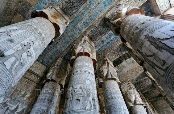 "[EGYPT 29524]'Outer hypostyle hall of Hathor Temple at Dendera.'	The columns in the outer hypostyle hall (or pronaos) of the Hathor Temple at Dendera are crowned by four-sided capitals carved with the face of the cow-eared goddess. The faces symbolize the four cardinal points of the universe and stress the universal character of the sky goddess Hathor, who was also called ""Lady with the four Faces""The ceiling has recently been cleaned of soot and dust and is decorated with a complex set of astro"