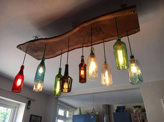 Bespoke bottle chandelier made with oak, glass bottles and retro Edison light bulbs for a unique centre piece. The price is for a mixture of 10 bottles on an oak frame and a chain link structure to hang. Includes Edison bulbs. Shipping to be arranged depending on location and size of