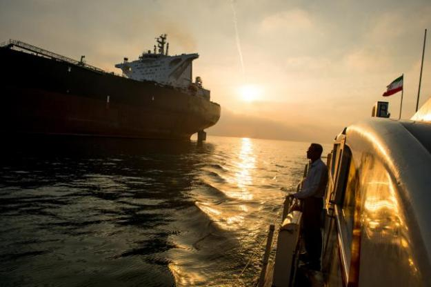 © Bloomberg. A support vessel flying an Iranian national flag sails alongside the oil tanker 'Devon' as it prepares to transport crude oil to export markets in Bandar Abbas, Iran, on Friday, March 23, 2018. Geopolitical risk is creeping back into the crude oil market. Photographer: Ali Mohammadi/Bloomberg