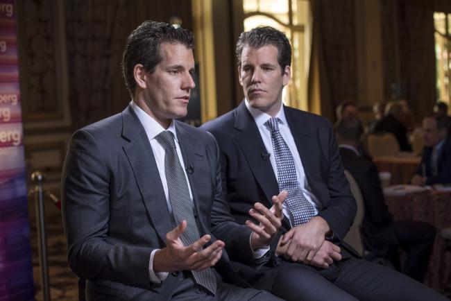 © Bloomberg. Cameron Winklevoss speaks as Tyler Winklevoss listens. Photographer: David Paul Morris/Bloomberg