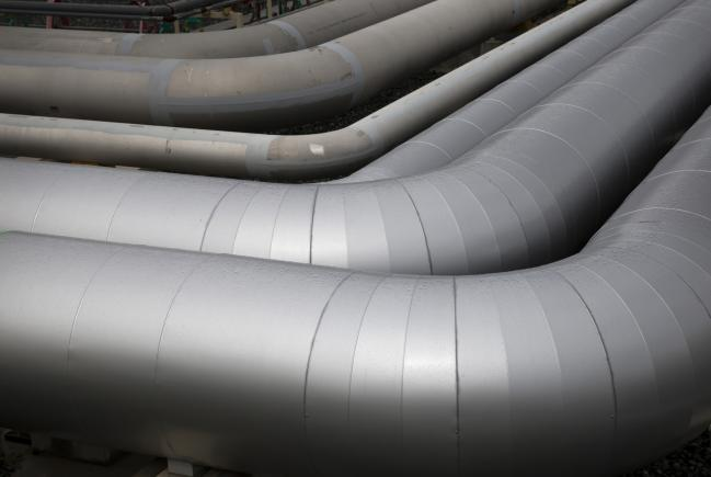 © Bloomberg. Gas pipes sit near a liquefied natural gas (LNG) storage tank under construction at Tokyo Electric Power Co.'s (Tepco) Futtsu gas-fired thermal power plant in Futtsu, Chiba Prefecture, Japan, on Monday, Sept. 10, 2018. Japan will maintain a target for clean energy to account for as much as 24 percent of the countrys power mix by 2030, according to a long-term plan approved by the Cabinet in July.