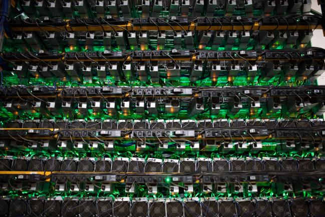 © Bloomberg. Cryptocurrency mining rigs sit on racks at a Bitfarms facility in Saint-Hyacinthe, Quebec, Canada. Photographer: James MacDonald/Bloomberg