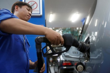 © Reuters. FILE PHOTO: An employee pumps petrol into a car at a petrol station in Hanoi