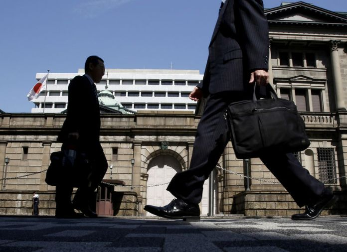 © Reuters. FILE PHOTO - People walk on a street in front of the Bank of Japan headquarters in Tokyo