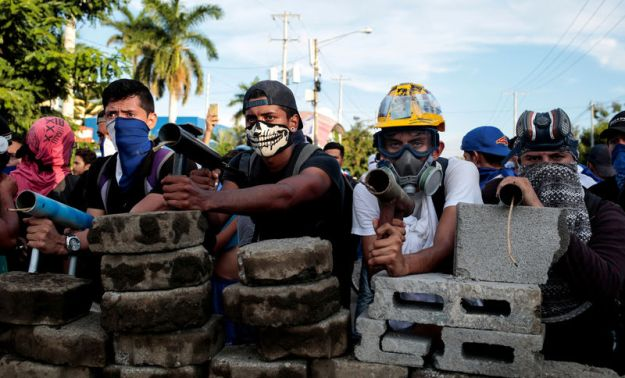 © Reuters. Demonstrators stand behind a barricade during clashes with riot police during a protest against Nicaragua's President Daniel Ortega's government in Managua