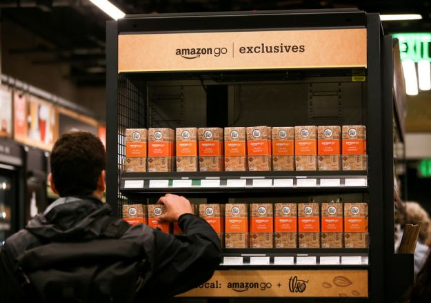 © Reuters. FILE PHOTO: A customer selects an Amazon Go-branded Theo chocolate bar in the new Amazon Go store in Seattle