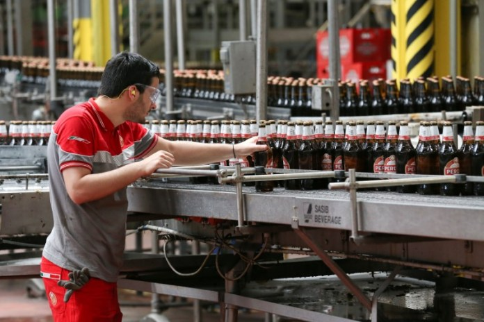 © Reuters. A worker inspects bottles of beer on the production line at the Birra Peroni beer factory in Rome
