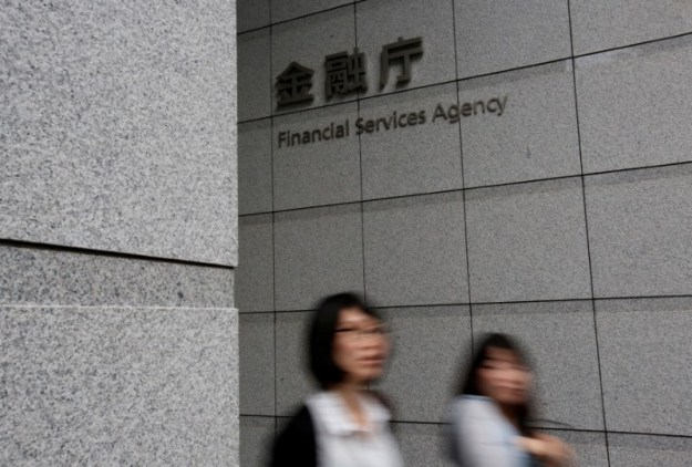 © Reuters. FILE PHOTO: Women walk under a sign of Japan's Financial Services Agency in Tokyo, Japan