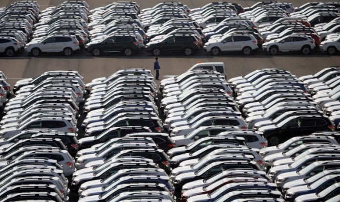 © Reuters. A worker is seen among newly manufactured cars awaiting export at port in Yokohama