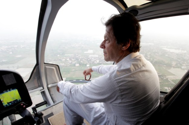 © Reuters. Imran Khan, chairman of the Pakistan Tehreek-e-Insaf (PTI), political party, holds his tasbih, or prayer beads, as he sits in a helicopter on his way to a campaign rally ahead of general elections in Narowal
