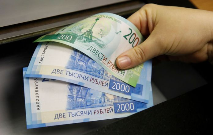 © Reuters. FILE PHOTO: A woman holds new 200 and 2,000 rouble banknotes in a bank in Moscow