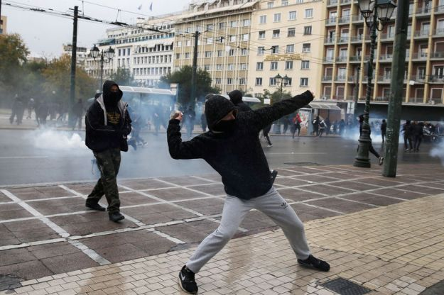 © Reuters. A protester throws a rock during an anniversary rally marking the 2008 police shooting of 15-year-old student Alexandros Grigoropoulos, in Athens