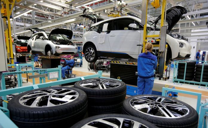 © Reuters. FILE PHOTO: A worker mounts a tyre at the serial production BMW i3 electric car in the BMW factory in Leipzig