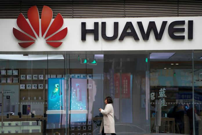 © Reuters. Eine Frau geht an einem Huawei-Logo in einem Einkaufszentrum in Shanghai vorbei