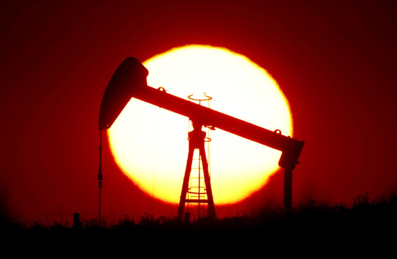 © Reuters. FILE PHOTO: The sun sets behind a pump-jack outside Saint-Fiacre
