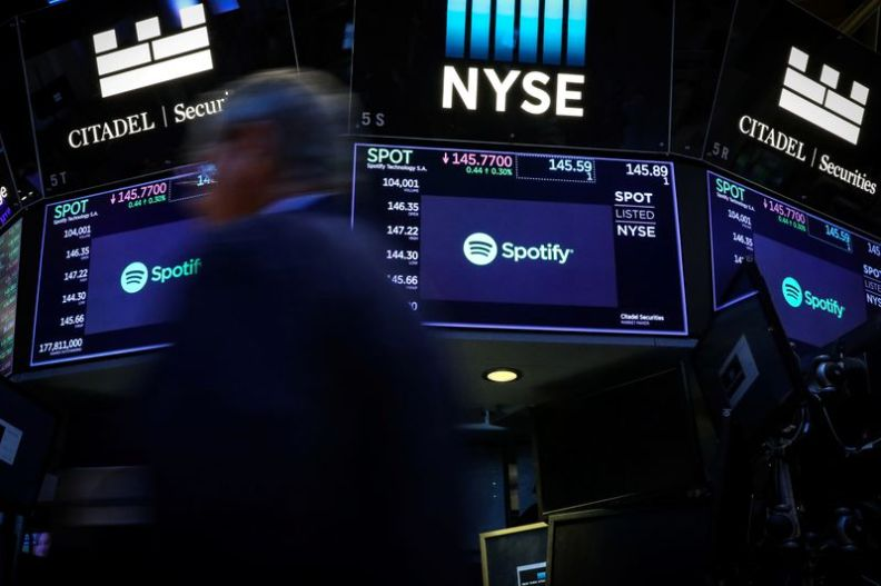 © Reuters. A trader passes by screens showing Spotify on the floor at the NYSE in New York