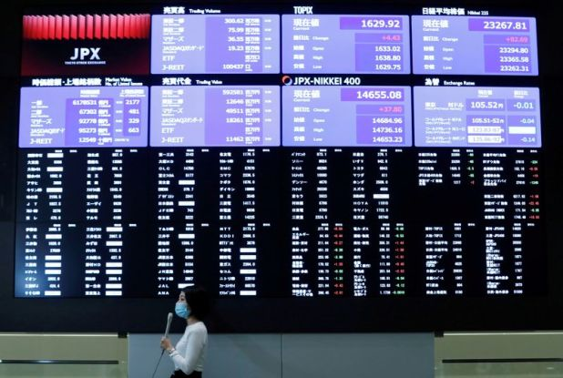 Reuters.  File photo: A TV reporter stands in front of a big screen on the Tokyo Stock Exchange after the market opened in Tokyo.