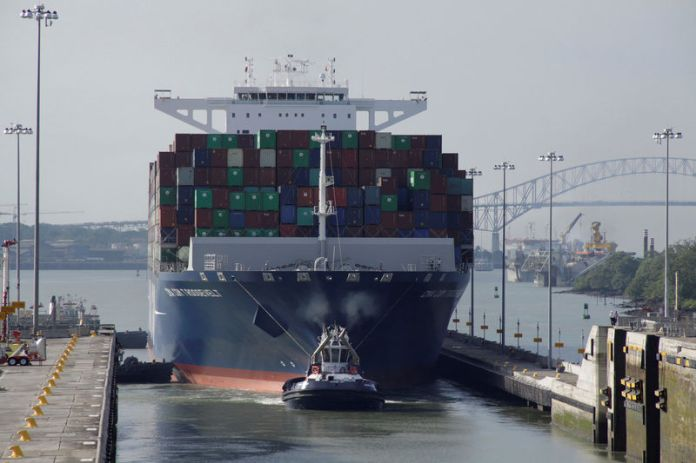 © Reuters. FILE PHOTO: Tugboat tows the British CMA CGM T. Roosevelt cargo vessel at Panama Canal