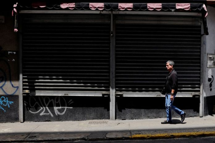 © Reuters. A man walks past closed stores in Caracas