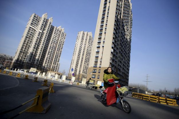 © Reuters. A woman rides past a residential compound in Beijing's Tongzhou district