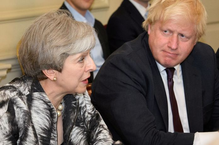© Reuters. FILE PHOTO: Britain's Prime Minister Theresa May sits next to Britain's Foreign Secretary Boris Johnson as she holds the first Cabinet meeting following the general election at 10 Downing Street, in London