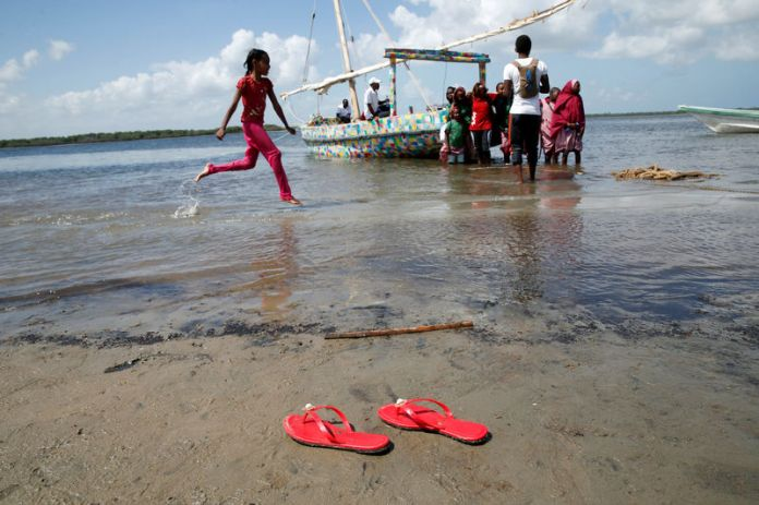 © Reuters. Girl runs past Flipflopi the first dhow boat made entirely of recycled plastic during its launch ceremony on the island of Lamu