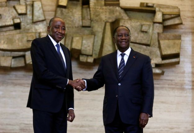 © Reuters. FILE PHOTO: Ivory Coast President Alassane Ouattara and new Prime Minister Amadou Gon Coulibaly pose for pictures in the Presidential Palace in Abidjan