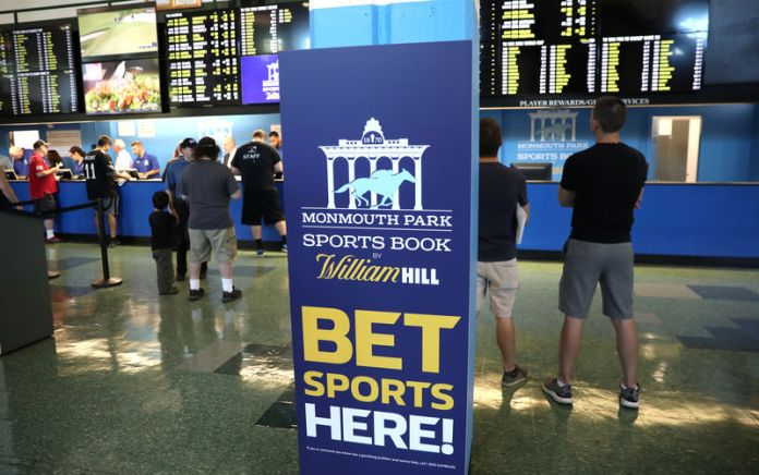 © Reuters. Gamblers place bets on sports at Monmouth Park Sports Book by William Hill, shortly after the opening of the first day of legal betting on sports in Oceanport