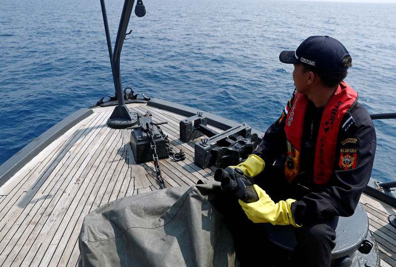 © Reuters. FILE PHOTO: Indonesian customs officers patrol at a search area for Lion Air flight JT610 in Karawang waters