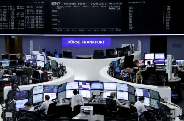 © Reuters. Traders work at their desks in front of the German share price index, DAX board, at the stock exchange in Frankfurt