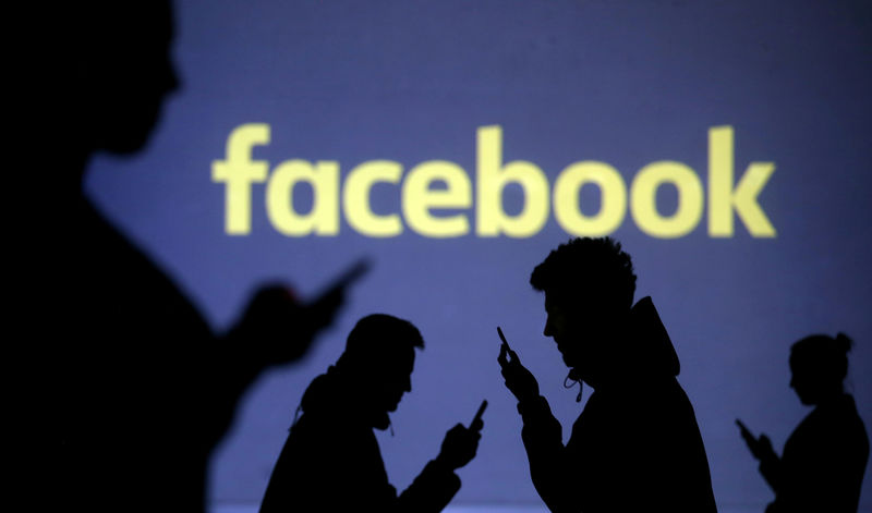 © Reuters. FILE PHOTO: Silhouettes of mobile users are seen next to a screen projection of the Facebook logo in this picture illustration